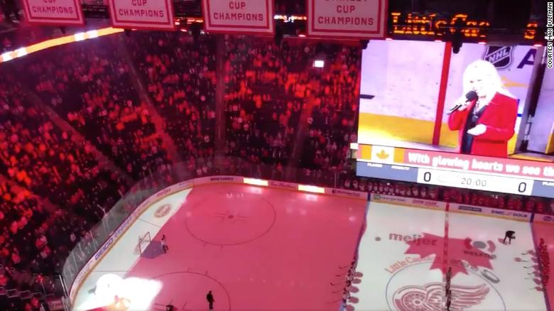 Hockey fans help sing national anthem when singer's microphone fails